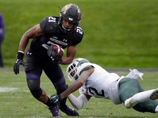 FILE - In this Oct. 28, 2017, file photo, Northwestern running back Justin Jackson, left, is tackled by Michigan State cornerback Justin Layne during the first half of an NCAA college football game in Evanston, Ill. Jackson, Northwestern's career rushing leader, needs 156 yards to join Wisconsin great Ron Dayne as the only Big Ten players with four 1,000-yard seasons. (AP Photo/Nam Y. Huh, File)