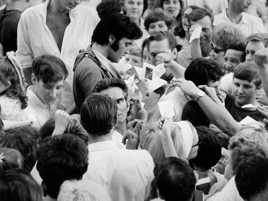 Elvis Presley signs autographs at Graceland on Sunday,