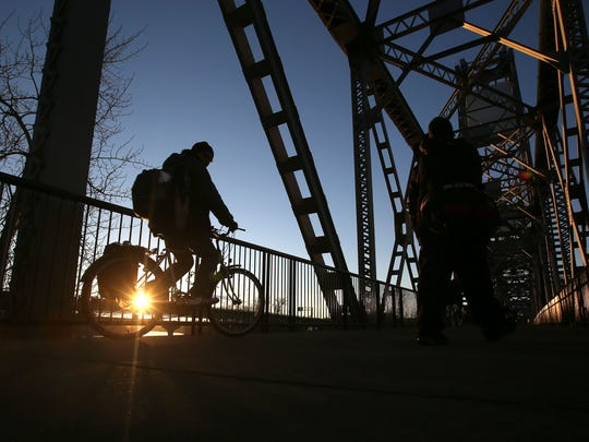 A cyclist rides across the Union Street Bridge under blue skies on Tuesday, Jan. 13, 2015, Salem, Ore.