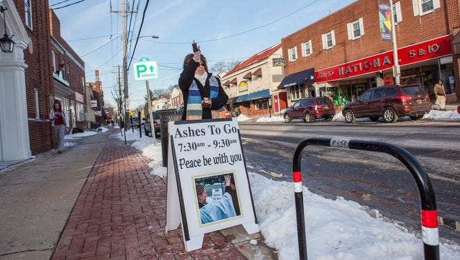 """The Rev. Cynthia Robinson, of New Ark United Church of Christ, moves a sign out by the sidewalk on Main Street in Newark so more passersby could see the offer of """"Ashes to Go"""" on Ash Wednesday. """"For me, this is what it means to be a Christian. It is for us to show up where the people are,"""" Robinson said."""