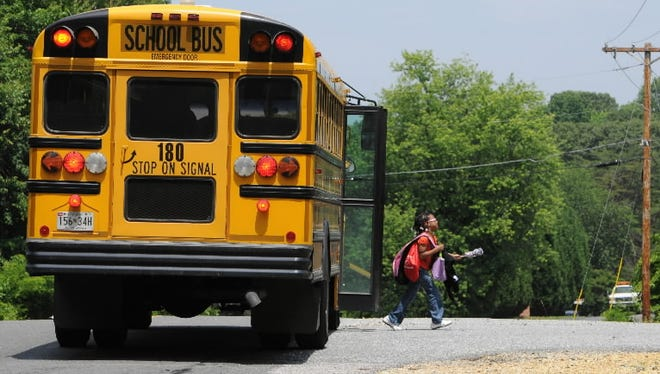 A girl gets off the bus on her way home from school in Charles County, Md.