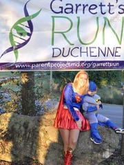 Garrett Sapp, an 8-year-old boy from Columbia, Tenn., who has Duchenne muscular dystrophy sits with his mom, Amber Sapp. The family, dressed as super heroes, puts on a fundraising run every year to support research for Duchenne. This is from the 2013 Garrett's Hero Run.