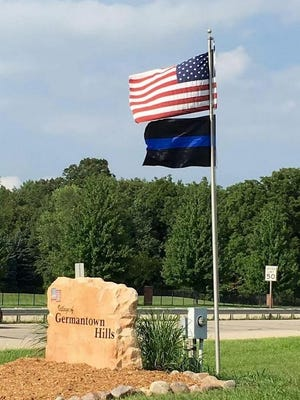 The thin-blue-line flag flies below the American one at one of the entrances to Germantown Hills, along Illinois Route 116. A group of residents is attempting to persuade the village to add more flags on public property or take down the pro-police flag instead.