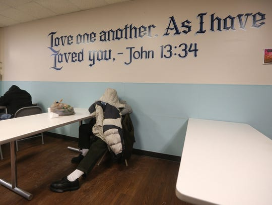 A man gets warm and rests at the Open Door Mission,
