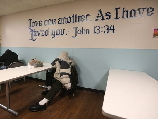 A man gets warm and rests at the Open Door Mission, under scripture written on the wall. The facility will stay open 24 hours for both men and women.  The frigid temperatures are expected to end Monday with a high in the mid-30'.