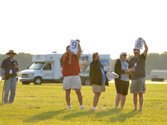 Judges score the balloons as they aim for the targets at the Field of Flight Thursday night.