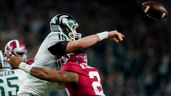 Michigan State quarterback Connor Cook (18) is hit