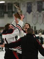 Conor Burnette (21) raises the regional trophy.