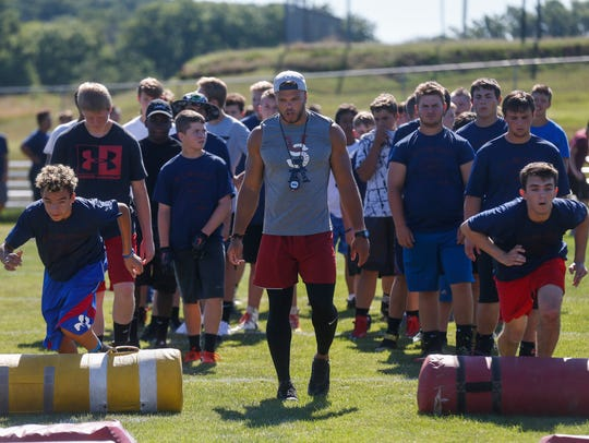 Dylan Cole runs a drill during his football camp at