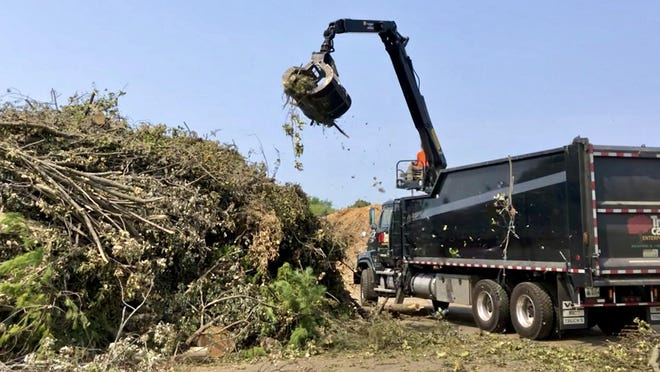 A tree care company unloads tree branches on Monday at a designated tornado debris site at Rock Valley College in Rockford.