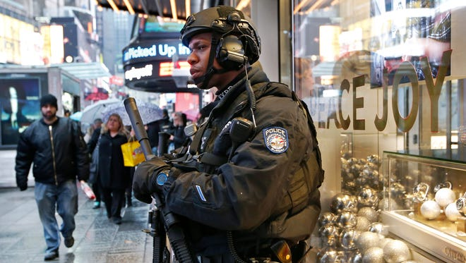 A heavily armed counterterrorism officer takes shelter Dec. 29, 2016, beneath an overhang above a store in Times Square in New York.