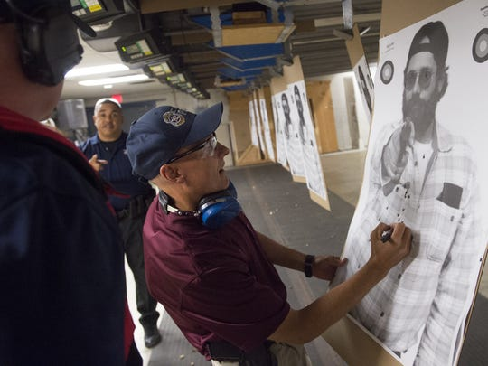 Sgt. Joel Tower makes notes on a target during a firearms training exercise at the Fort Collins Police Services shooting range Sept. 27.