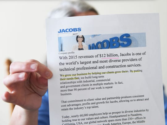 Janie Clark holds a printout from Jacobs Engineering
