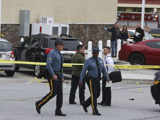 Police investigate at the scene after a state police