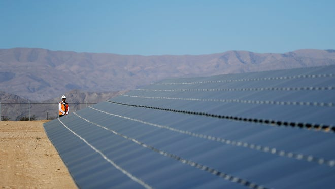 FILE- In this Sept. 15, 2016, file photo, a man stands at the end of a solar panel array on the Moapa River Indian Reservation about 40 miles northeast of Las Vegas. Elected officials and tribal leaders helped Friday, March 17, 2017, to power up the vast sun-to-electricity array that, in 2012, was the first utility-scale power production plant approved by the U.S. Interior Department on Indian land nationwide.
