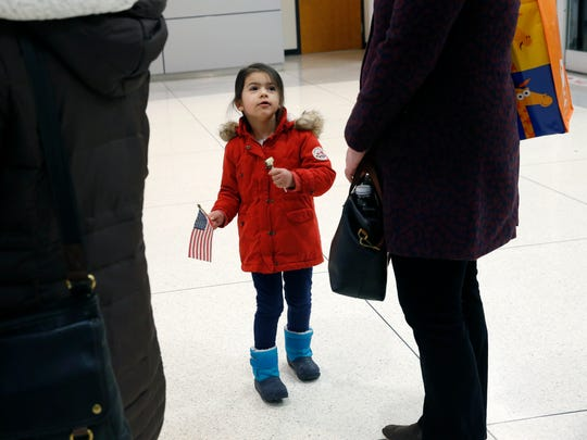 Ariana Dupre la Tour-Powell, of Rochester waits with an American Flag for the arrival of Afghani interpreter Naqeebullah Malikzada and his family at the Greater Rochester International Airport.