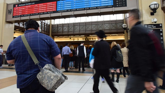 Passengers rush through the turnstiles after transferring to a PENN Station bound train at the Secaucus Junction Monday morning.