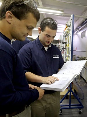 Garrett Richards, left, from Oakland High School and Jonathon Cudney, right, from Siegel High School work on an electrical training board as the two participate in a mechatronics internship at Nissan in 2015.