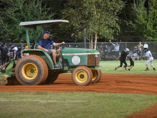 Volunteer James Hawley tills a baseball infield as football teams practice in the outfield at the Navarre Youth Sports Association in Navarre on Wednesday, October 11, 2017.