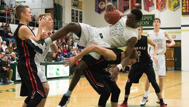 Iowa City West High's Wali Parks is fouled as he comes down with an offensive rebound during the Trojan's 77-71 victory over Linn-Mar in Iowa City. Friday, January 15, 1016.