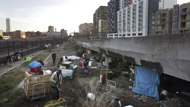 Homeless pack up their belongings in February before the San Francisco Department of Public Works, in concert with Caltrans and law enforcement, cleared out their camp.