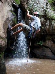 A climber goes canyoneering at Big Bradley Falls with