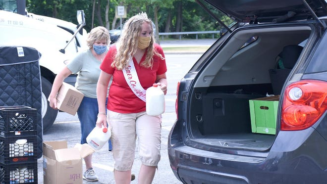 Herkimer County Dairy Princess Katie Livingston delivers two gallons of milk to a car in Herkimer while her mother Karen Livingston prepares to add a box of chicken during a giveaway Tuesday, June 30, 2020.