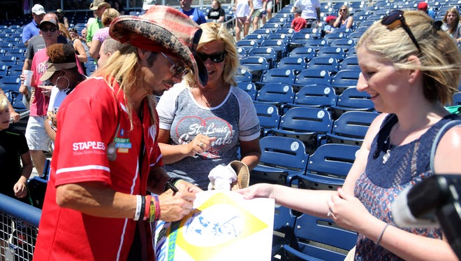 Bret Michaels signs autographs a poster for Danielle Ritcheyat the 26th annual City of Hope Celebrity Softball Game on Tuesday at First Tennessee Park.