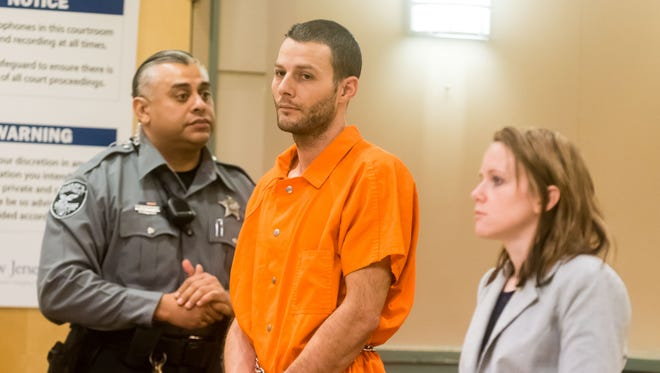 Murder defendant Jeremiah E. Monell stands for his pre-trial detention hearing at Cumberland County Superior Court in Bridgeton on Monday, January 9.  Public Defender Lindsey Seidel is at his left.