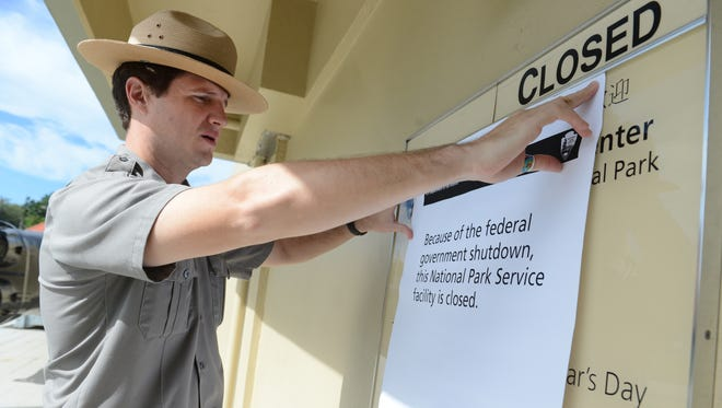 In this October 2013 file photo, Ben Hayes, park ranger at War in the Pacific National Historical Park, posts a sign at the entrance to the T. Stell Newman Visitor Center. The center, along with other National Park visitor facilities on island including park restrooms and parking lots, were closed as the partial shutdown of the federal government went into effect nationwide. Another shutdown of the federal government is in effect.