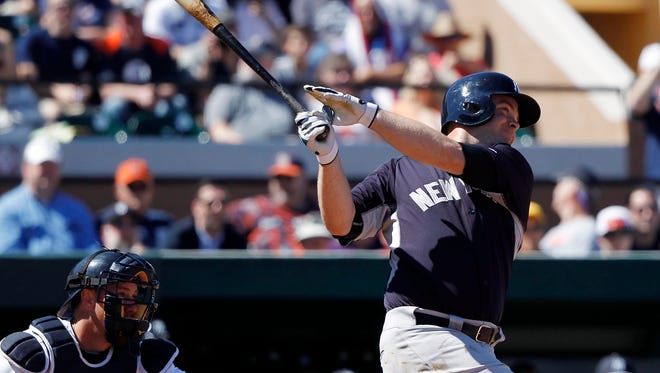 New York Yankees catcher Brian McCann (34) hits a solo home run during the second inning against the Detroit Tigers.