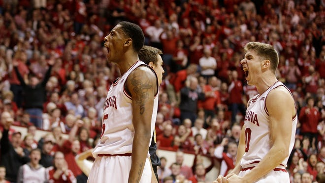 Indiana's Troy Williams (5) and Collin Hartman (30) celebrate after Williams made a shot and was fouled during the second half of an NCAA college basketball game against Iowa, Thursday, Feb. 11, 2016, in Bloomington, Ind. Indiana won 85-78.