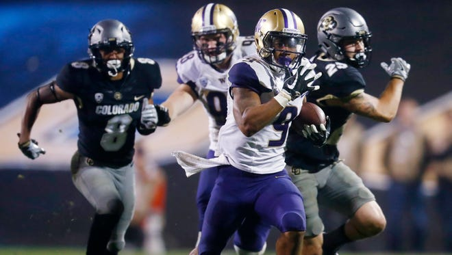 Washington running back Myles Gaskin, front, dashes past Colorado defensive backs Trey Udoffia, left, and Ryan Moeller on the way to a touchdown during Saturday's game.