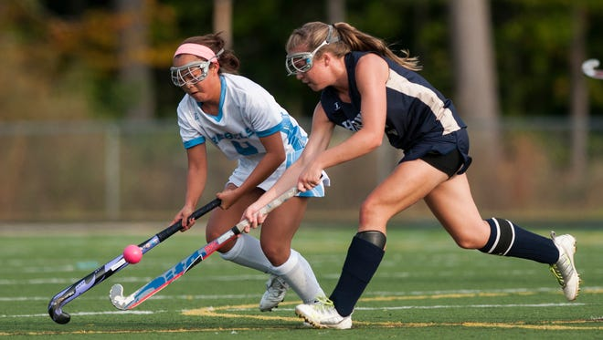 Essex's Kathleen Young (9) battles for the ball with South Burlington's XiXi Halvorson-Phelan (4) during the girls varsity field hockey game Tuesday.