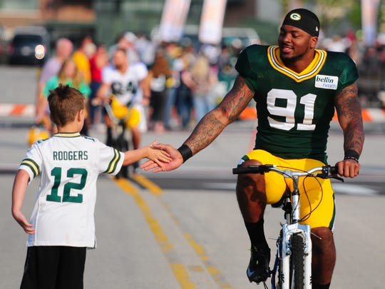 Green Bay Packers linebacker Jayrone Elliott is greeted by Sawyer Princl, of Green Bay, before training camp practice.