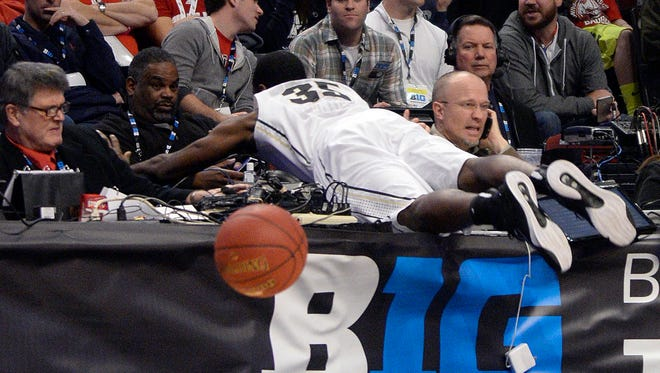 Purdue Boilermakers guard Rapheal Davis dives for a loose ball and clobbers Star sports columnist Gregg Doyel during the second half of the game against the Penn State Nittany Lions. Purdue won 64-59; Gregg's OK.
