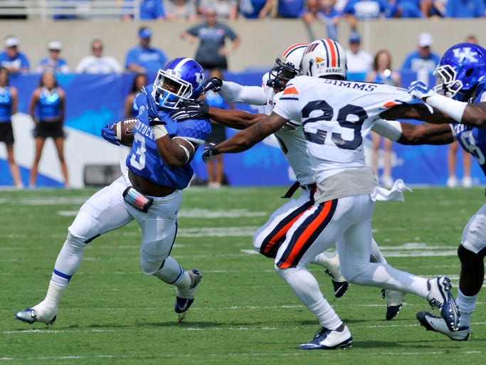 UK's Jojo Kemp rushes against UT Martin's Leon Carlton III and Jordan Brown, Saturday, Aug. 30, 2014 at Commonwealth Stadium in Lexington. Photo by Tim Webb, Special to the CJ