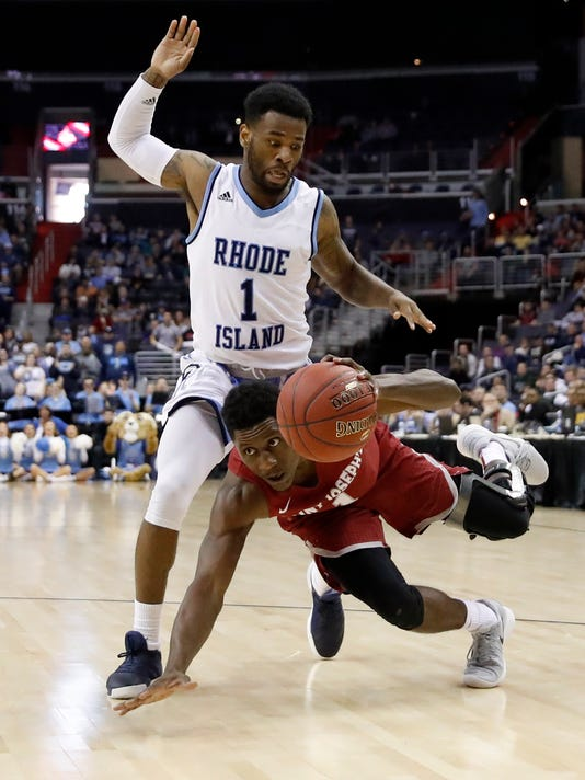 Rhode Island guard Jarvis Garrett (1) stands as Saint Joseph's guard Shavar Newkirk (1) falls but keeps possession of the ball during the second half of an NCAA college basketball game in the semifinals of the Atlantic 10 Conference tournament, Saturday, March 10, 2018, in Washington.  Rhode Island won 90-87. (AP Photo/Alex Brandon)
