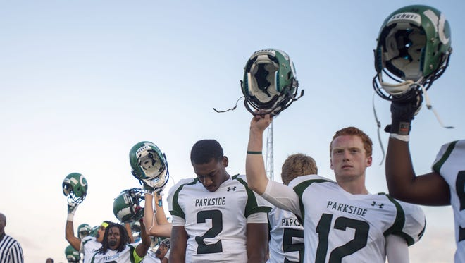 The Parkside Rams lift their helmets as the national anthem comes to an end and the game against Bennett begins at Wicomico County Stadium Friday, September 19 in Salisbury. Parkside defeated Bennett 33-14.