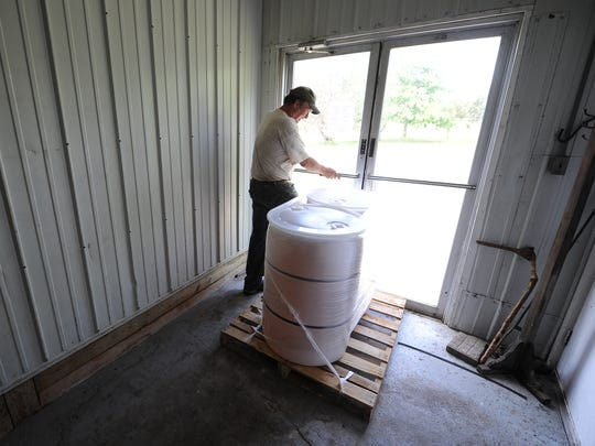 Century Sun Oil founder Dale Johnson walks past two 55-gallon drums of sunflower oil waiting to be shipped from his rural Shawano County farm.