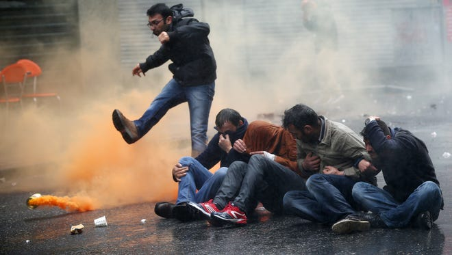 A demonstrator kicks a smoke canister as others try to protect themselves from the effects of tear gas, fired by riot police officers during clashes in Istanbul, Turkey, on May 1, 2015.