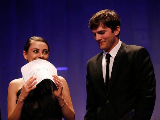 Actress Mila Kunis holds her certificate making her