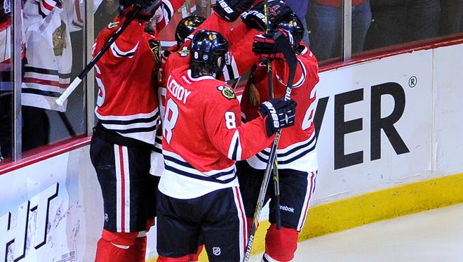 Chicago Blackhawks center Michal Handzus (26) is congratulated by his teammates after scoring the game-winning goal against the Los Angeles Kings during the second overtime in game five of the Western Conference Final of the 2014 Stanley Cup Playoffs at United Center.
