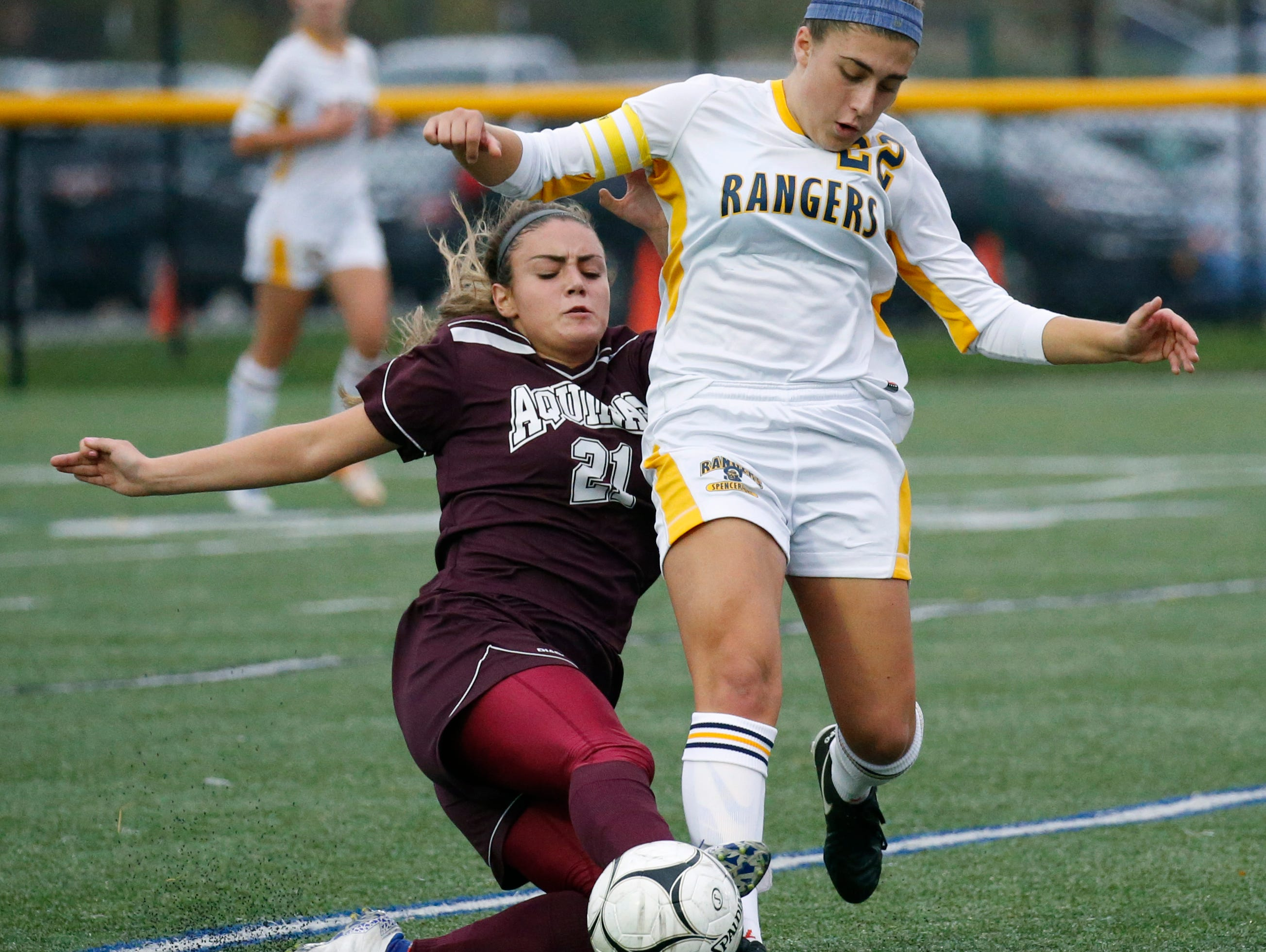 Aquinas' Regan Nugent reaches for the ball in front of Spencerport's Olivia Wall in the first half at Webster Schroeder High School.