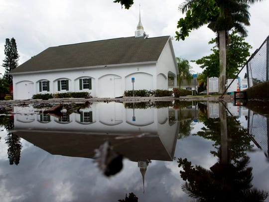 Heavy rains the previous day caused significant flooding around Iglesia Pentecostes Peniel along 107th Avenue in Naples Park on Wednesday, July 12, 2017. By midday most of the water had been pumped out, but more rain showers were expected.