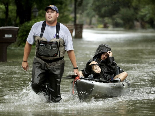 People evacuate a neighborhood inundated by floodwaters