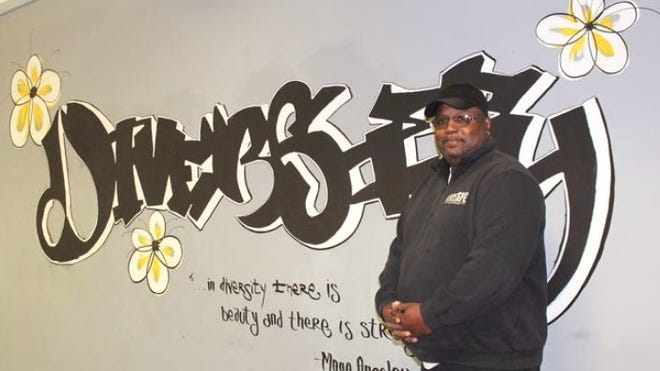 Pastor Willie Watt stands in front of a mural at East Ministries in Holland in 2018. The ministry's Board of Directors accepted Watt's resignation earlier this month.