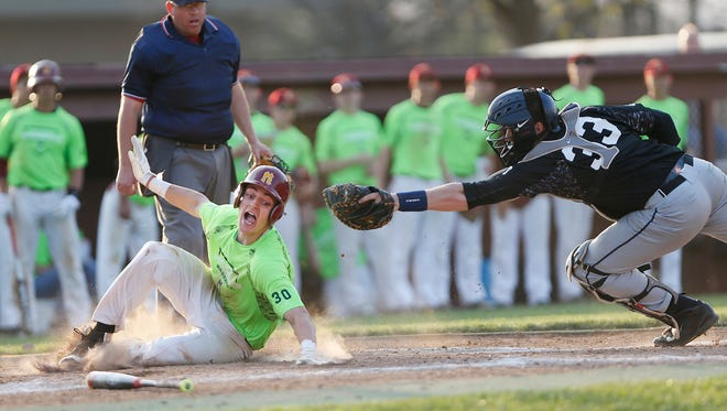 McCutcheon's Kelden Tyson dives beneath the tag of Harrison catcher Stohne Stetler to score and tie the game at 5-5 in the bottom of the sixth inning Tuesday, April 19, 2016, at McCutcheon High School. McCutcheon beat their county rival 7-6 in eight innings.