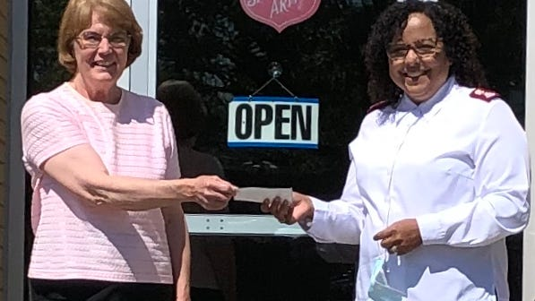 Homelessness Task Force member Linda Smith, left, presents Salvation Army Major Madelaine Dwier with a $1,275 check to help support the Salvation Army's new Living Room Project.