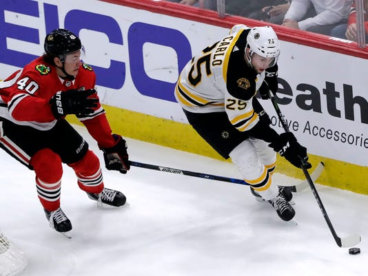 Boston Bruins defenseman Brandon Carlo, right, controls the puck against Chicago Blackhawks right John Hayden during the second period of an NHL hockey game Sunday, March 11, 2018, in Chicago. (AP Photo/Nam Y. Huh)